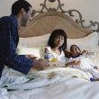 African American father bringing breakfast in bed to mother and son — Stock Photo