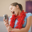 Hispanic girl singing into microphone in bedroom — Stock Photo