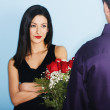 Young man giving skeptical girlfriend flowers — Stock Photo