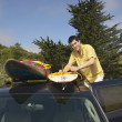 Man tying surfboard to car rack — Stock Photo