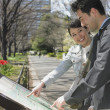 Asian couple looking at map in urban park — Stock Photo