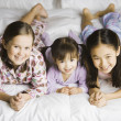 Stock Photo: Portrait of three girls laying on bed