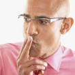 Portrait of a businessman with two fingers on his lips - Stock Photo