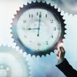 Stock Photo: Businessmtouching cog wheel with clock face in center