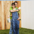 Multi-ethnic couple painting fence — ストック写真