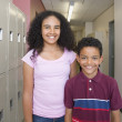 Girl and boy smiling in school hallway — Stock Photo #13230363