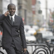 Businessman walking while talking on cell phone — Stock Photo