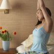 Stock Photo: Womstretching on side of bed