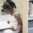 Girl reading book in library - Stockfoto