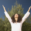 Young woman raising arms outdoors — Stock Photo