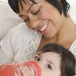 Hispanic mother feeding baby with bottle — Stock Photo