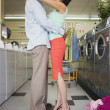 Couple hugging at laundromat — Stock Photo #13230421