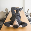 Businessman lying on table — Stock Photo #13230462
