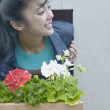 Asian woman leaning out window with flowerbox — Stock Photo
