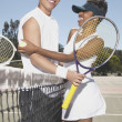 Portrait of couple hugging on tennis court - Stock Photo