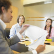 Stock Photo: Businesswomen holding papers in meeting