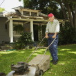 Portrait of elderly man mowing lawn — ストック写真