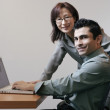 Businesspeople using a laptop in office area — Stok fotoğraf