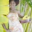 Portrait of woman standing next to banana tree holding bananas — Stock Photo