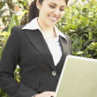 Hispanic businesswoman using laptop outdoors — Stock Photo