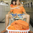 Womhugging relaxed boyfriend in laundromat — Stock Photo #13230547