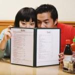 Asian couple reading menu at restaurant — Stock Photo