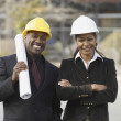 AfricAmericbusinesspeople with blueprints — Stock Photo #13230556