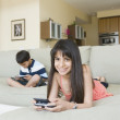 Hispanic siblings playing handheld video games - Stockfoto