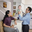Couple playing with their baby in the kitchen - Stock Photo