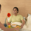 Stock Photo: Young woman serving boyfriend breakfast in bed
