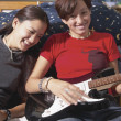 Teenage girls playing the electric guitar — Stock Photo
