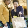 Mixed Race women with shopping bags - Foto Stock
