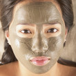 Stock Photo: Young womposing with mud mask facial