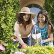 Hispanic mother and daughter watering flowers — Stok Fotoğraf #13230725