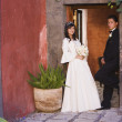 Hispanic girl in Quinceanera dress with chamberlain - Foto Stock