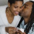 Stock Photo: Africcouple exchanging gift and kissing