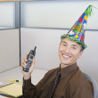 Stock Photo: Asibusinessmwearing birthday hat