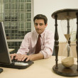 Hispanic businessman looking at hourglass on desk — Stockfoto