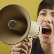 Asian businesswoman yelling into megaphone — Stock Photo