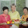 Women holding plates of fruits and vegetables — Stock Photo