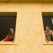 Couple looking at each other from different windows - Stock Photo