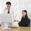Stock Photo: Businessmand businesswomworking with time zone clocks on wall behind them