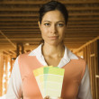 Hispanic woman holding paint swatches at construction site — Stock Photo