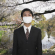 Asian businessman wearing surgical mask in park — Stock Photo