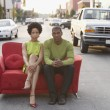 Young couple sitting on a couch outdoors - 图库照片