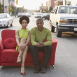 Young couple sitting on a couch outdoors — ストック写真