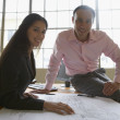 Businesspeople examining blueprints — Stockfoto