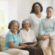 Multi-generational African women sitting on sofa - Stock Photo