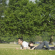 Young couple lounging in grass — Stok fotoğraf