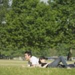 joven pareja descansando en la hierba — Foto de Stock